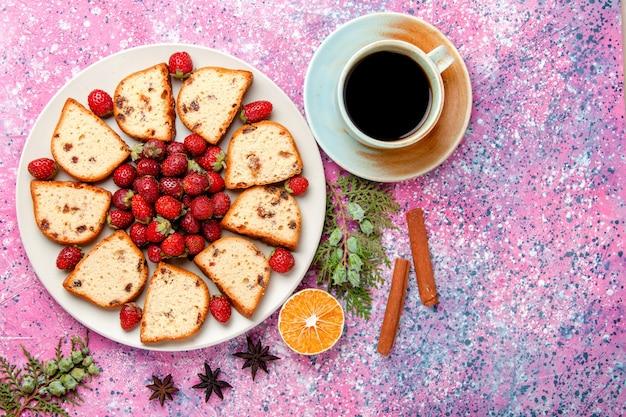 Вид сверху на кусочки торта со свежей красной клубникой и чашкой кофе на розовом столе. выпечка сладкого бисквитного пирога с сахарным печеньем.