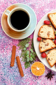 Вид сверху на кусочки торта со свежей красной клубникой и чашкой кофе на розовой поверхности. выпечка сладкого бисквитного цвета.