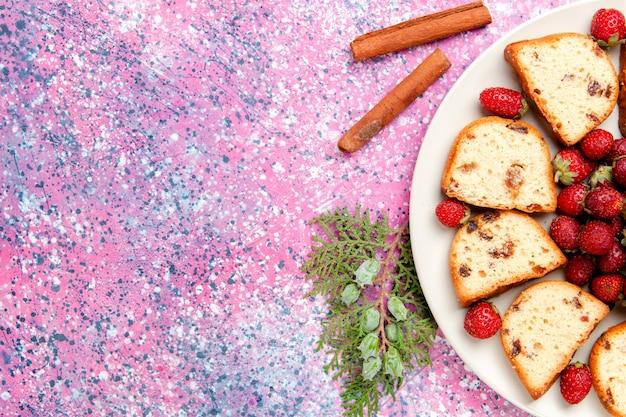 ピンクのbackgrouondケーキに新鮮な赤いイチゴと甘いビスケット色のパイシュガークッキーを焼く上面図ケーキスライス