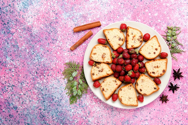 ピンクのデスクケーキに新鮮な赤いイチゴのトップビューケーキスライスは甘いビスケット色のパイシュガークッキーを焼く