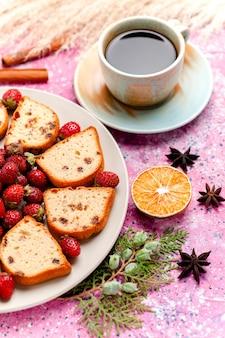 ピンクのbackgruondケーキに新鮮なイチゴとコーヒーを添えた上面のケーキスライスは、甘いビスケット色のパイシュガークッキーを焼きます
