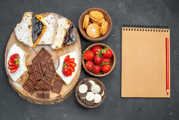 Top view cake slices with fruits cookies and choco bars on dark surface