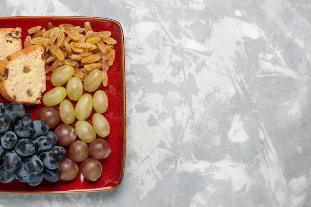 Вид сверху на кусочки торта с виноградом и изюмом внутри красной тарелки на белой поверхности