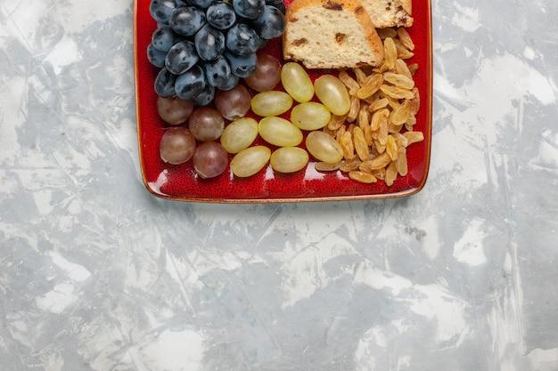 白い表面の赤いプレートの中にブドウとレーズンが入った上面図のケーキスライス