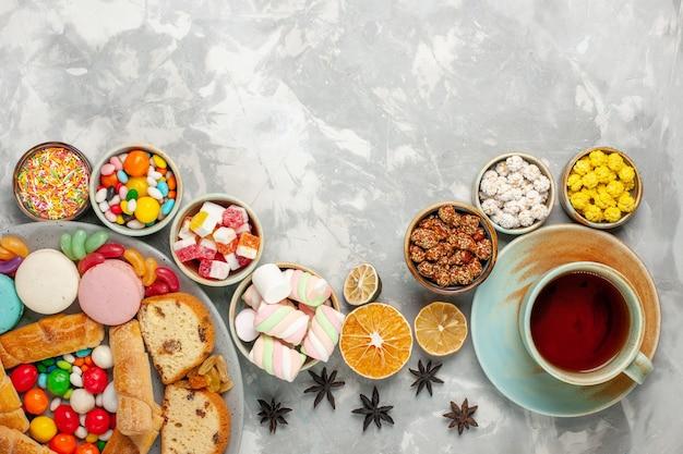 Vista dall'alto di fette di torta con macarons, bagel e caramelle con una tazza di tè sul tavolo bianco