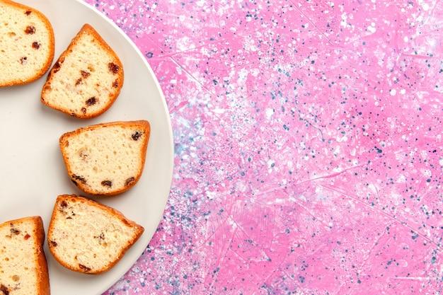 Вид сверху кусочки торта с изюмом внутри тарелки на розовом фоне торт выпечка сладкого бисквитного цвета пирог сахарное печенье