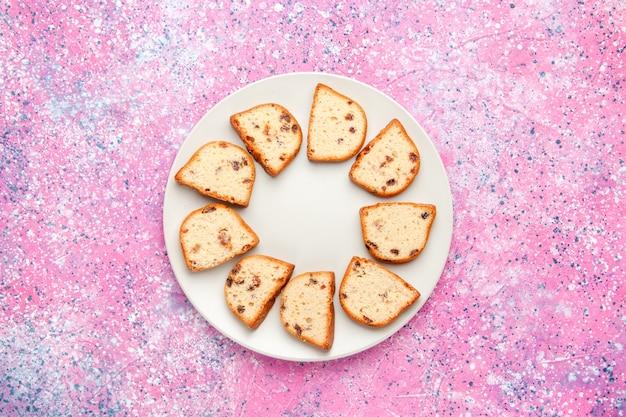 ピンクの背景のケーキのプレートの内側にレーズンが入った上面のケーキスライスは、甘いビスケット色のパイシュガークッキーを焼きます