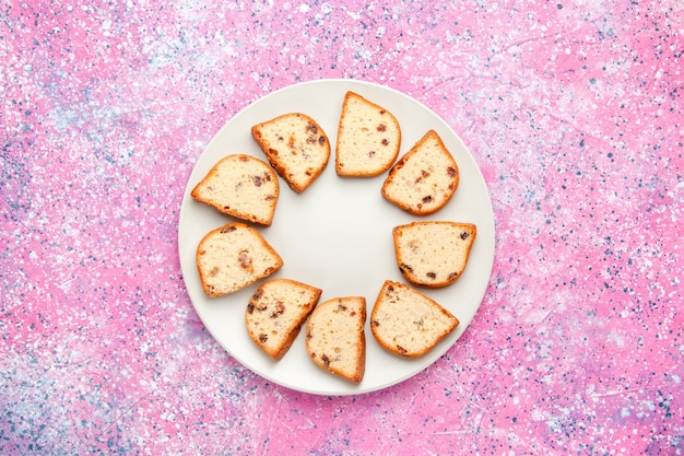 Fette di torta vista dall'alto con uvetta all'interno della piastra sullo sfondo rosa torta cuocere biscotti dolci biscotti di zucchero a torta di colore