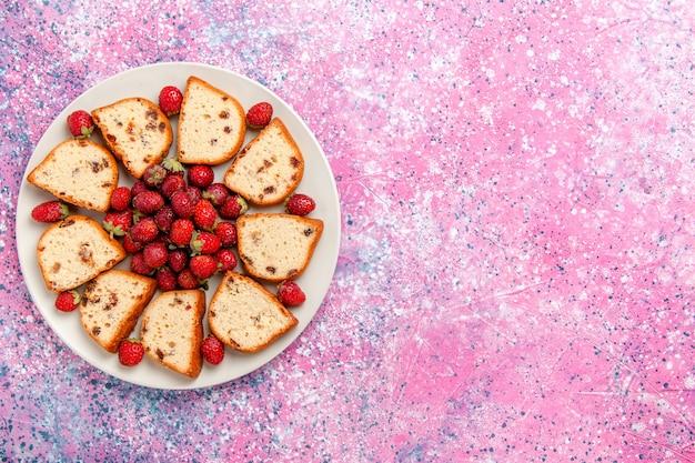 Вид сверху кусочки торта с изюмом внутри тарелки со свежей красной клубникой на розовом фоне выпечка торта сладкого цвета бисквита пирог сахарное печенье