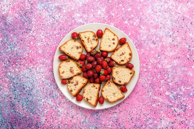 Fette di torta vista dall'alto con uvetta all'interno della piastra con fragole fresche sulla superficie rosa torta cuocere biscotti dolci biscotti color zucchero
