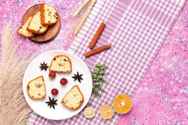 ピンクの背景のケーキにイチゴとシナモンのトップビューケーキスライスは甘いビスケット色のパイシュガークッキーを焼く