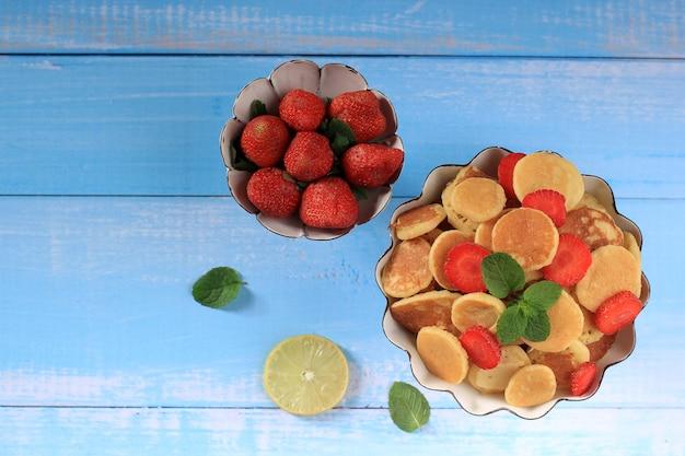白い背景にミントの葉を飾った、小さなパンケーキシリアルとイチゴのトップビューケーキスタンド。トレンディな料理。ミニシリアルパンケーキ。景観オリエンテーション