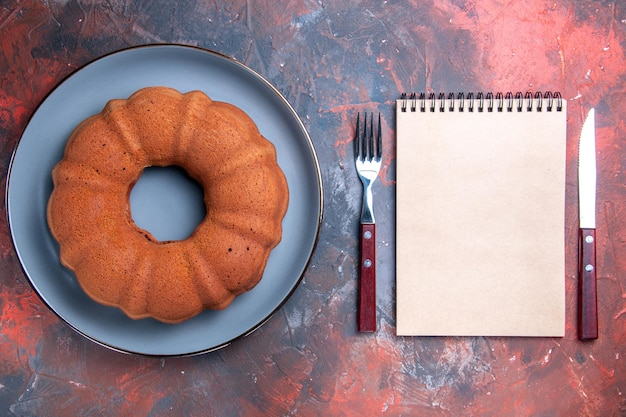 Top view cake white notebook fork and knife next to the appetizing cake on the plate