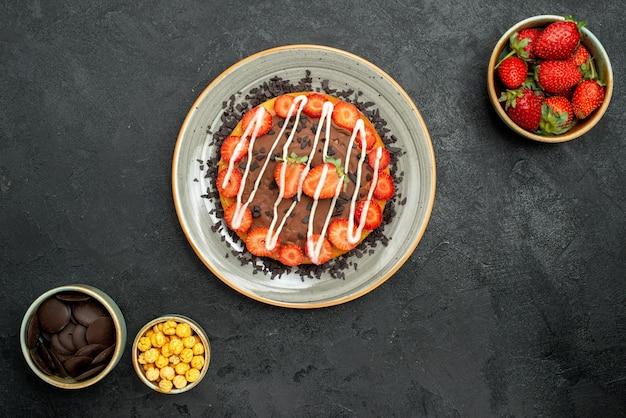 어두운 테이블에 있는 딸기 헤이즐넛과 초콜릿 그릇 사이에 초콜릿과 딸기가 있는 초콜릿 케이크가 있는 탑 뷰 케이크