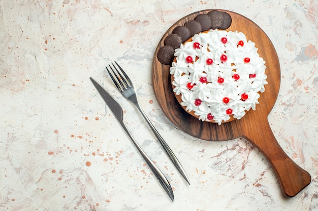 Torta vista dall'alto con cioccolato e crema pasticcera bianca su tagliere in legno