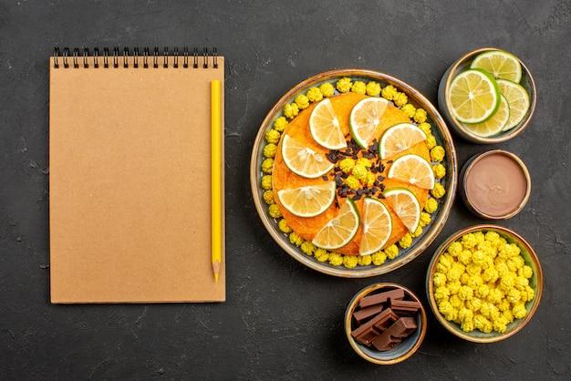 ノートブックの横にあるチョコレートと柑橘系の果物の食欲をそそるケーキと黒いテーブルの上のライムチョコレートとチョコレートクリームのスライスの鉛筆ボウルのトップビューケーキ