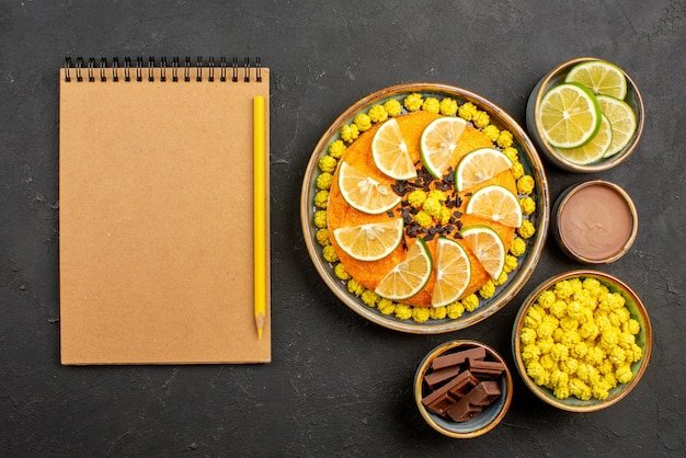 Top view cake with citrus fruits appetizing cake with chocolate and citrus fruits next to the notebook and pencil bowls of slices of lime chocolate and chocolate cream on the black table