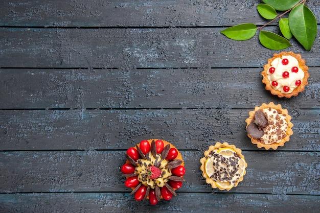 コピースペースのある暗い木製のテーブルにコーネルフルーツラズベリーとチョコレートタルトの葉とトップビューケーキ