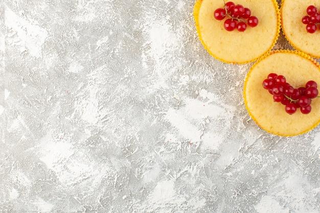 Вид сверху торт с клюквой вкусный и отлично пропеченный на светлом фоне торт бисквитный сахар сладкий