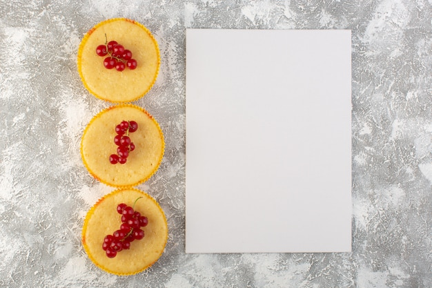 Top view cake with cranberries yummy and perfectly baked with paper blank on the light background cake biscuit sweet
