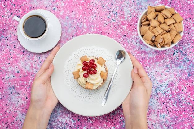 Вид сверху торт со сливками, держащийся женщиной с чашкой кофе на цветном столе, торт, бисквитный сахар, сладкий цвет