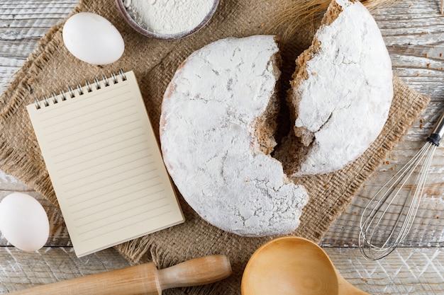 Торт вид сверху с блокнот, яйца, скалкой на мешок ткани и деревянной поверхности. горизонтальный