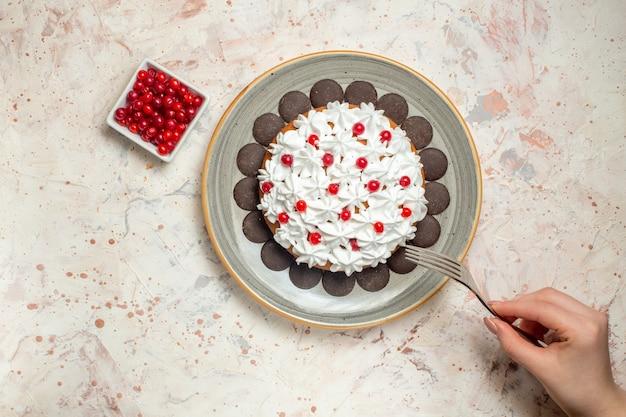 女性の手でボウルフォークにペストリークリームとチョコレートベリーのトップビューケーキ