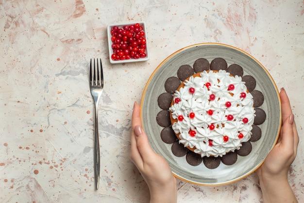 ボウルフォークの女性の手のベリーのペストリークリームとチョコレートのトップビューケーキ