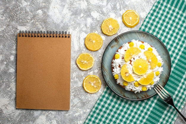 グリーンホワイトチェッカーテーブルクロスの大皿にペストリークリームとレモンフォークのトップビューケーキ。空のノートブック