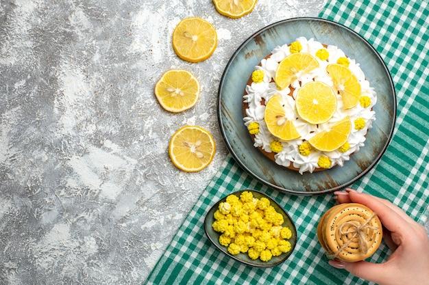 緑の白い市松模様のテーブルクロスのボウルに女性の手のキャンディーの大皿クッキーにペストリークリームとレモンのトップビューケーキ