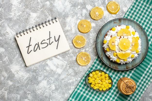 緑の白い市松模様のテーブルクロスレモンのボウルにロープキャンディーで結ばれた大皿クッキーにペストリークリームとレモンのトップビューケーキ