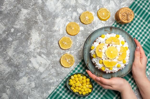 緑の白い市松模様のテーブルクロスのボウルに女性の手のクッキーキャンディーの大皿にペストリークリームとレモンのトップビューケーキ