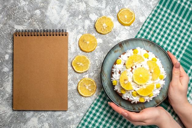 緑の白い市松模様のテーブルクロスの上の女性の手で大皿にペストリークリームとレモンのトップビューケーキ