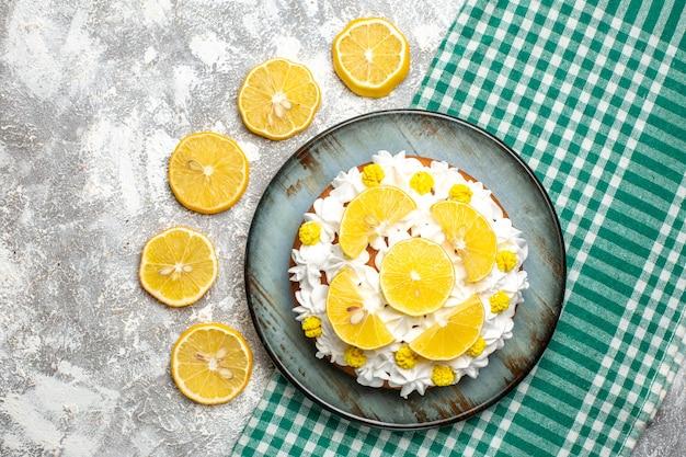 グリーンホワイトチェッカーテーブルクロスの大皿にペストリークリームとレモンのトップビューケーキ