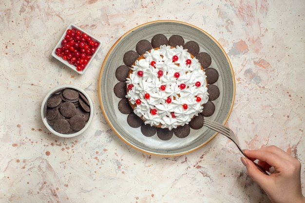 Top view cake with pastry cream berries and chocolate in bowls fork in female hand