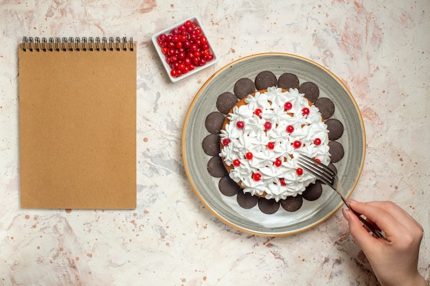 Top view cake with pastry cream and chocolate berry in bowl fork in female hand notebook