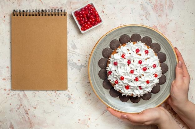 Torta vista dall'alto con crema pasticcera e cioccolato in bacche di mano femminile in ciotola e taccuino vuoto