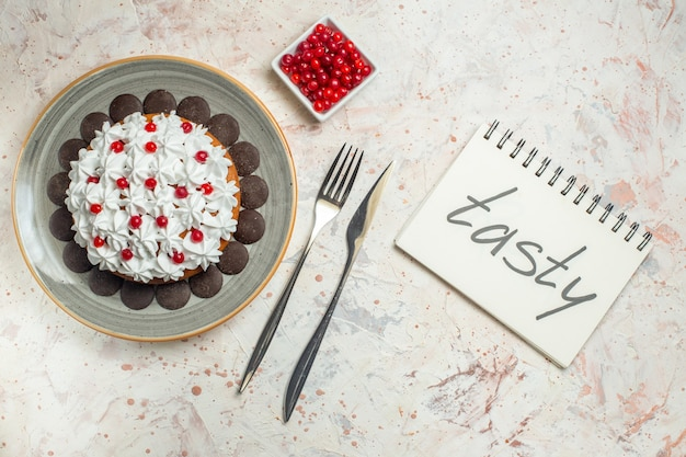Top view cake with pastry cream and chocolate fork and dinner knife berries in bowl tasty written on notebook