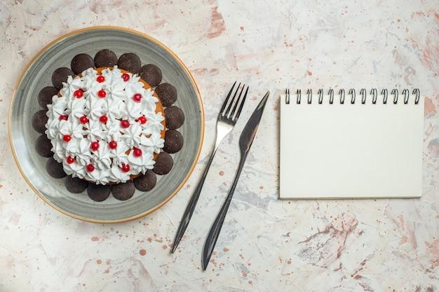 Torta vista dall'alto con crema pasticcera e forchetta al cioccolato e taccuino con coltello da cena