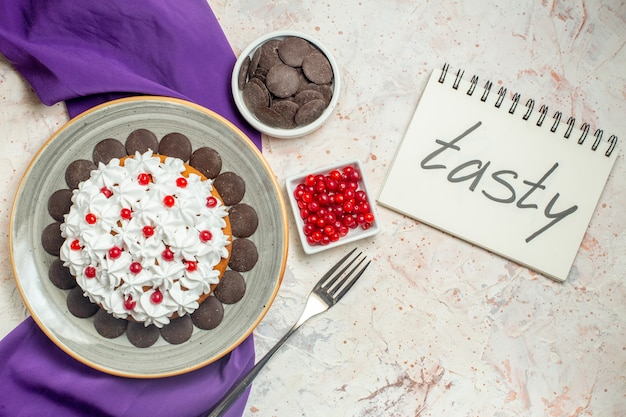 Top view cake with pastry cream and chocolate on plate purple shawl bowls with chocolate and berries fork tasty written on notebook