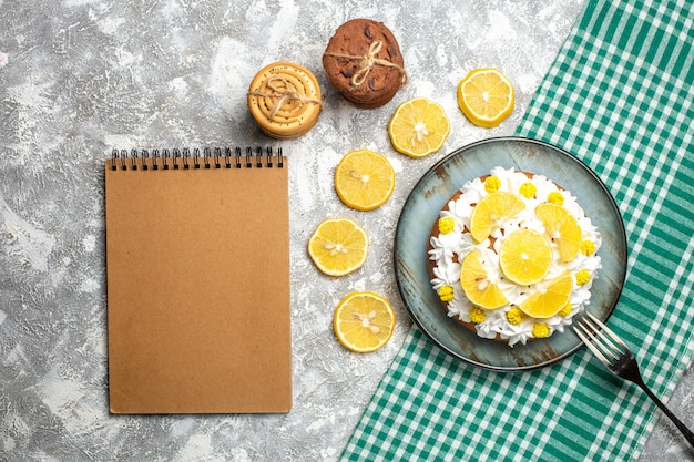 Top view cake with pastry cream and lemon fork on platter on green white checkered tablecloth. empty notebook