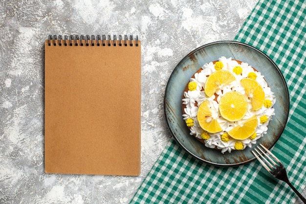 Top view cake with pastry cream and lemon on plate a fork on green white checkered tablecloth. empty notebook