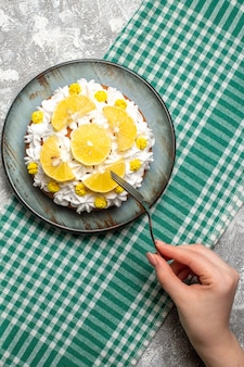 Top view cake with pastry cream and lemon on round plate fork in female hand on green white checkered tablecloth