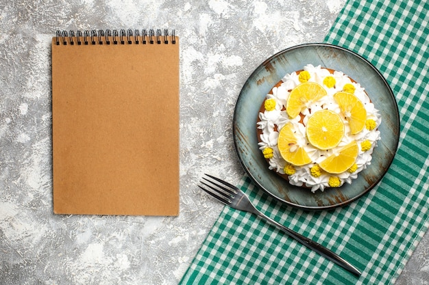 Top view cake with pastry cream and lemon on round plate fork on green and white checkered kitchen towel. empty notebook