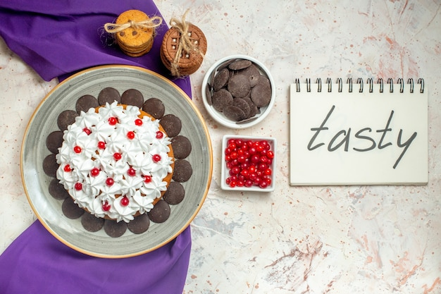 ノートに書かれたおいしいボウルにロープチョコレートとベリーで結ばれた楕円形のプレート紫のショールクッキーにペストリークリームとトップビューケーキ