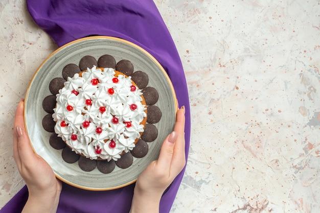 女性の手の紫色のショールのプレートにペストリークリームとトップビューケーキ