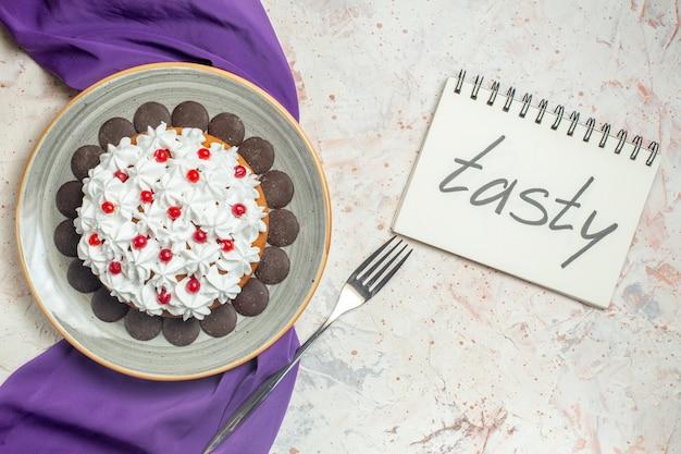 Вид сверху торт с кондитерским кремом на тарелке, фиолетовая шаль, вилка, вкусно написано в блокноте
