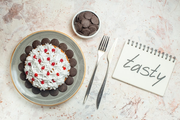 Top view cake with pastry cream on oval plate chocolate in bowl fork and dinner knife. tasty word written on notebook