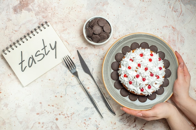 Top view cake with pastry cream on oval plate in female hand chocolate in bowl fork and dinner knife tasty written on notebook