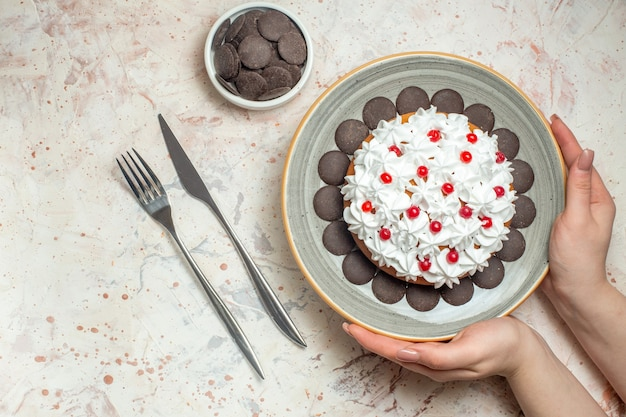 Top view cake with pastry cream on oval plate in female hand chocolate in bowl fork and dinner knife